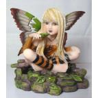 Figurine de fée assise buvant dans une feuille